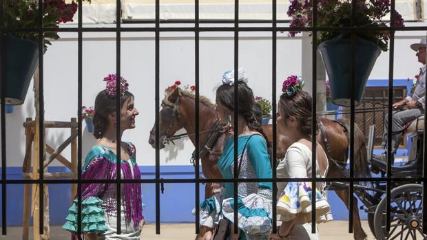 Tres jóvenes vistas a través de una caseta de la Feria de Nuestra Señora de la Salud