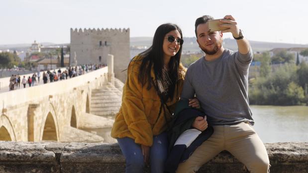 Una pareja de jóvenes turistas se fotografía con el Puente Romano y la Torre de la Calahorra al fondo