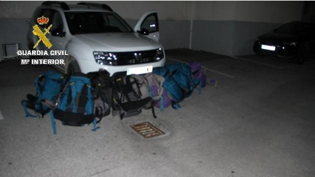 Imagen facilitada por la Guardia Civil del vehículo y de la mochiclas con hachís