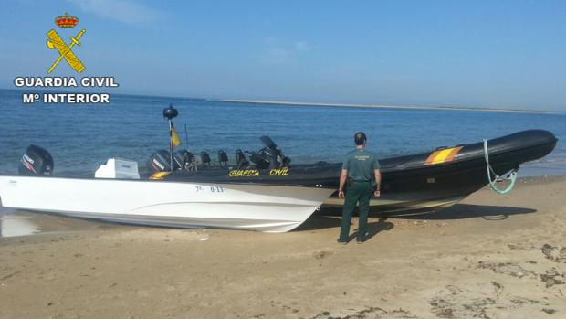 Un agente junto a una narcolancha en una playa de Huelva