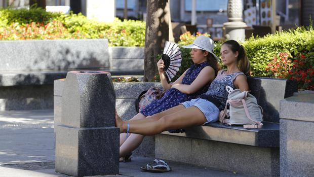 Dos turistas se refrescan en la plaza de Las Tendillas