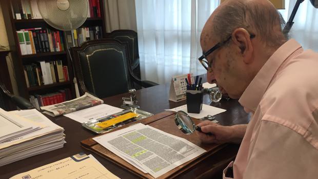 Un abogado escudriña con una lupa la letra pequeña de un contrato de crédito rápido