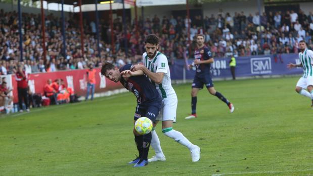 El central del Córdoba CF Fernando Román presiona ante el Yeclano Deportivo
