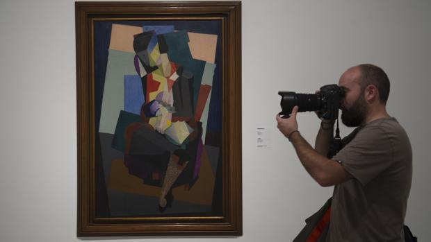 Un fotógrafo toma una imagen de una de las obras de la exposición