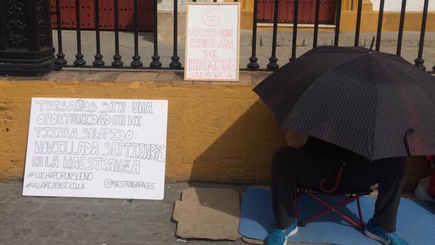 El novillero, cubierto bajo un paraguas, junto al cartel en el que exigía una novillada en San Miguel
