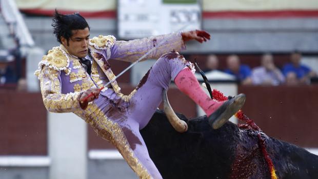 Diego San Román , en una fea voltereta, con el pitón a punto de hundirse en la piel