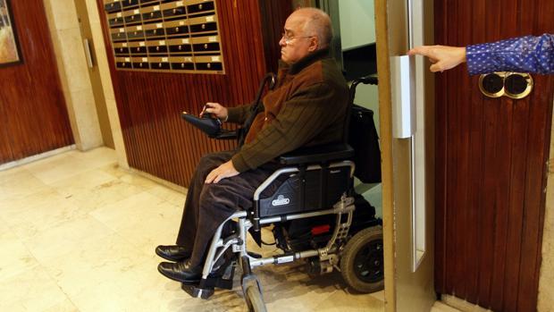 Un discapacitado sale de un ascensor en su bloque de pisos