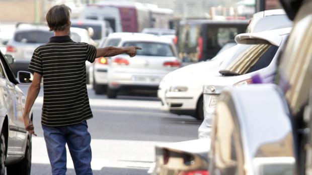 Imagen de un gorrilla aparcando coches en Sevilla