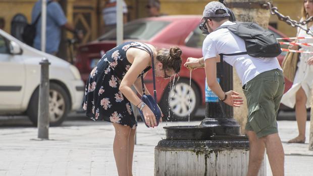 Unos turistas se resfrescan en una fuente en el centro de Sevilla