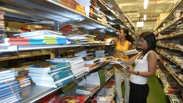 Una mujer busca llibros de texto en un comercio