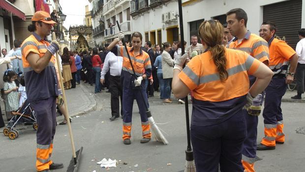 Varios operarios de Lipasam limpiando la calle tras pasar la hermandad del Buen Fin